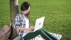 Junge intelligente Frauenmischrasse sitzt auf dem Plaid und dem Arbeiten stock footage