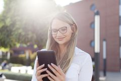 Junge intelligente Geschäftsfrau in den Brillen Mitteilung auf Tabelle lesend Lizenzfreie Stockbilder