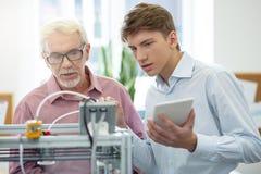 Junge internieren das Versuchen, Drucker 3D unter Überwachung laufen zu lassen stockfoto