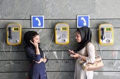 Junge iranische Frauen, die Öffentlichkeit und Handys verwenden lizenzfreie stockbilder