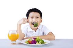 Junge, der den Brokkoli - lokalisiert isst stockbild