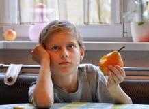 Junge isst eine Birne Stockfoto