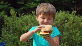 Junge isst einen großen Burger mit Käse stock footage