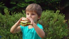 Junge isst einen großen Burger mit Käse stock video
