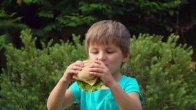 Junge isst einen großen Burger mit Käse stock video footage