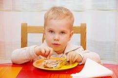 Junge isst Huhn Stockbild