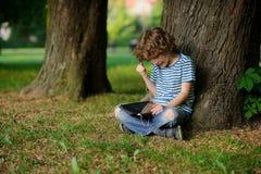 Junge ist auf Spiel an der Tablette scharf Stockfoto