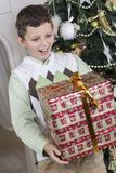 Junge ist mit einem großen Weihnachtsgeschenk überrascht Lizenzfreies Stockbild