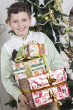 Junge ist mit vielen Weihnachtsgeschenken glücklich Lizenzfreie Stockbilder