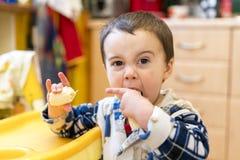 Junge 2 Jahre alte Essenbanane Baby 2 Jahre alt, eine Banane in der Küche essend Stockfotografie