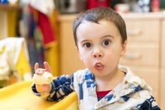 Junge 2 Jahre alte Essenbanane Baby 2 Jahre alt, eine Banane in der Küche essend Lizenzfreies Stockfoto