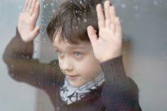 Junge 7 Jahre alte Junge, die neben dem Fenster stehen Stockbild