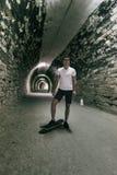 Junge 20-25 Jahre alte Mann im Tunnel mit Skateboard Umgebendes lig lizenzfreie stockfotos