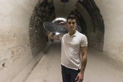 Junge 20-25 Jahre alte Mann im Tunnel mit Skateboard Umgebendes lig lizenzfreies stockfoto