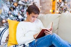Junge 10 Jahre auf der Couch, die ein Weihnachtsbuch liest Weihnachtsfeiertagskonzept Stockfotografie