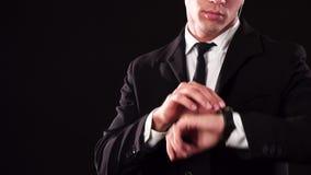 Junge James Bond überprüft seine Armbanduhr lizenzfreie stockfotos