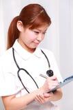 Junge Japanerkrankenschwester füllt medizinisches Diagramm Stockfotografie