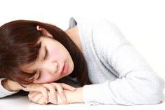 Junge japanische Frau, die auf dem Tisch schläft Lizenzfreie Stockfotografie
