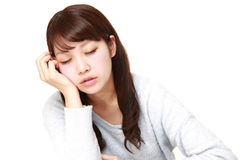 Junge japanische Frau, die auf dem Tisch schläft Lizenzfreies Stockfoto