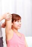 Junge japanische Frau, die Chiropraktik erhält Stockbilder