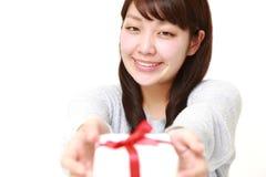 Junge japanische Frau, die ein Geschenk anbietet Stockfotos