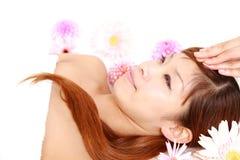 Junge japanische Frau, die eine Gesichtsmassage erhält Lizenzfreies Stockbild