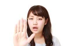 Junge japanische Frau, die Endgeste macht Lizenzfreie Stockfotos