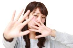 Junge japanische Frau, die Endgeste macht Stockfoto