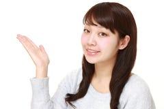 Junge japanische Frau, die etwas darstellt und zeigt Lizenzfreie Stockbilder