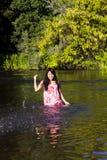 Junge japanische Frau, die Fluss-Kleiderdas lächeln spritzt Stockfoto