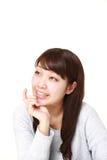 Junge japanische Frau, die an ihrer Zukunft träumt Stockfotografie