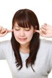 Junge japanische Frau leidet unter Geräuschen Stockfoto