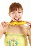 Junge japanische Frau mit gegrilltem Mais Stockbilder