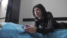 Junge jugendlich und des Steuerknüppelmannes mit Kapuze Strickjacke absorbiert im on-line-Videospiel Jungenjugendlicher im Hauben stock video footage