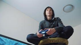 Junge jugendlich und des Steuerknüppelmannes mit Kapuze Strickjacke absorbiert im on-line-Videospiel Jungenjugendlicher in der Ha stock video footage