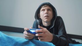 Junge jugendlich und Steuerknüppelmann cybersport mit Kapuze Strickjacke absorbiert im on-line-Videospiel Jungenjugendlicher im H stock video