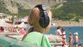 Junge Jugendliche, die durch den weißen Sandstrand hört Musik unter Verwendung der Kopfhörer und des Smartphone gegen ein Meer si stock video footage