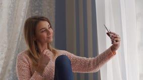 Junge Jugendliche, die Foto macht oder selfie in ihrem Schlafzimmer vor dem Fenster, Luxuswohnung macht stock video
