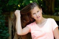 Junge Jugendliche im Park mit dem langen blonden Haar und Gesichtsausdruck lizenzfreie stockfotografie