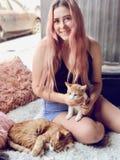 Junge Jugendliche mit dem langen Haar, das Haustierkatzen hält Lizenzfreie Stockfotos