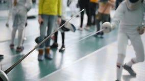 Junge Jugendlichefechter, die in der Halle auf einem fechtenden Turnier und einem Kämpfen stehen stock video footage