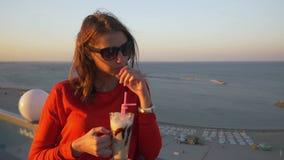 Junge Jugendlichfrau, die ein frappe auf der Terrasse mit einer Seeansicht trinkt stock video