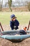 junge Jungen, die am Park an einem kalten Tag spielen Stockbild