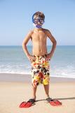 Junge Jungenhaltungen auf Strand Stockfoto