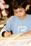 Junge Jungenzeichnung mit Zeichenstift Lizenzfreie Stockbilder