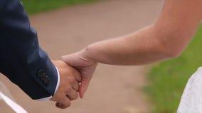 Junge Jungvermählten, die draußen gehen Die Braut und der Bräutigam gehen zusammen in den Park im Winter oder Sommer und Händchen Lizenzfreies Stockfoto