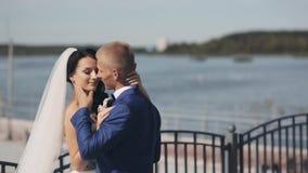 Junge Jungvermählten, die im Kai am Tag ihrer Hochzeitszeremonie stehen Schöne Braut und Bräutigam, die sich amüsiert stock video footage