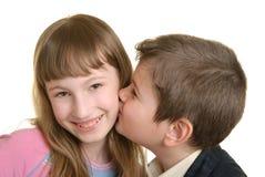 Junge küßt das Mädchen auf Backe Lizenzfreie Stockbilder