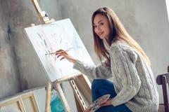 Junge Künstlerin, die zu Hause kreatives Malereibild malt stockfoto
