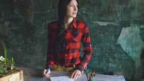 Junge Künstlerinmalereiskizze auf Papiernotizbuch mit Bleistift schaut im Fenster Lizenzfreie Stockfotografie